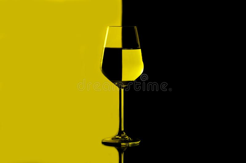 Wine glasses filled with water showing distortion. Black and yellow stock photography
