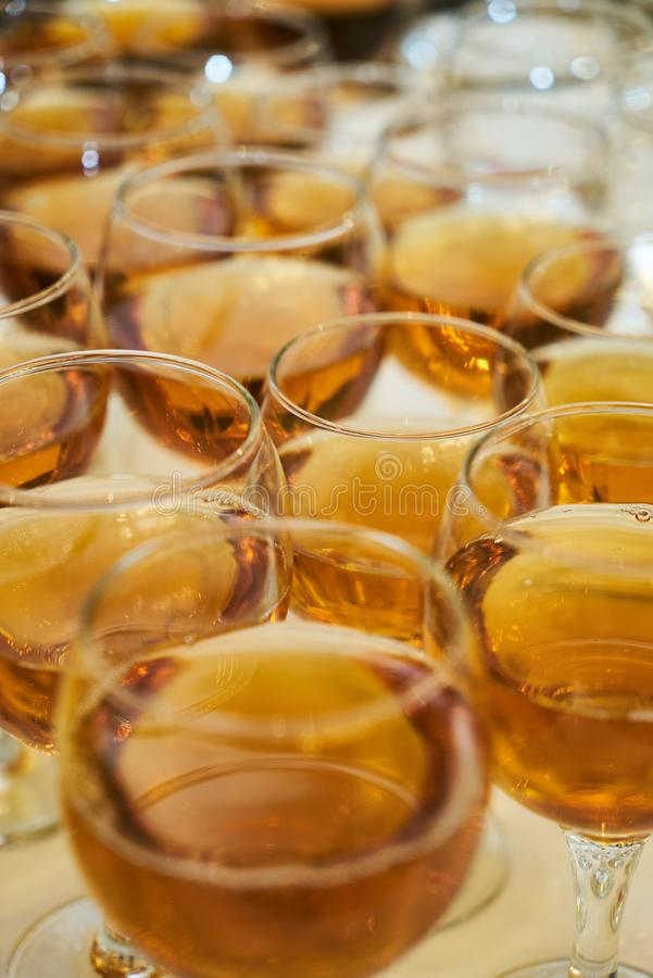 Wine glasses and orange juice glass on a white table background royalty free stock image