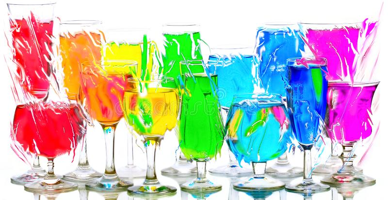 Wine glasses with red, orange, yellow, green, blue, violet liquids stand on a glass surface stock photos