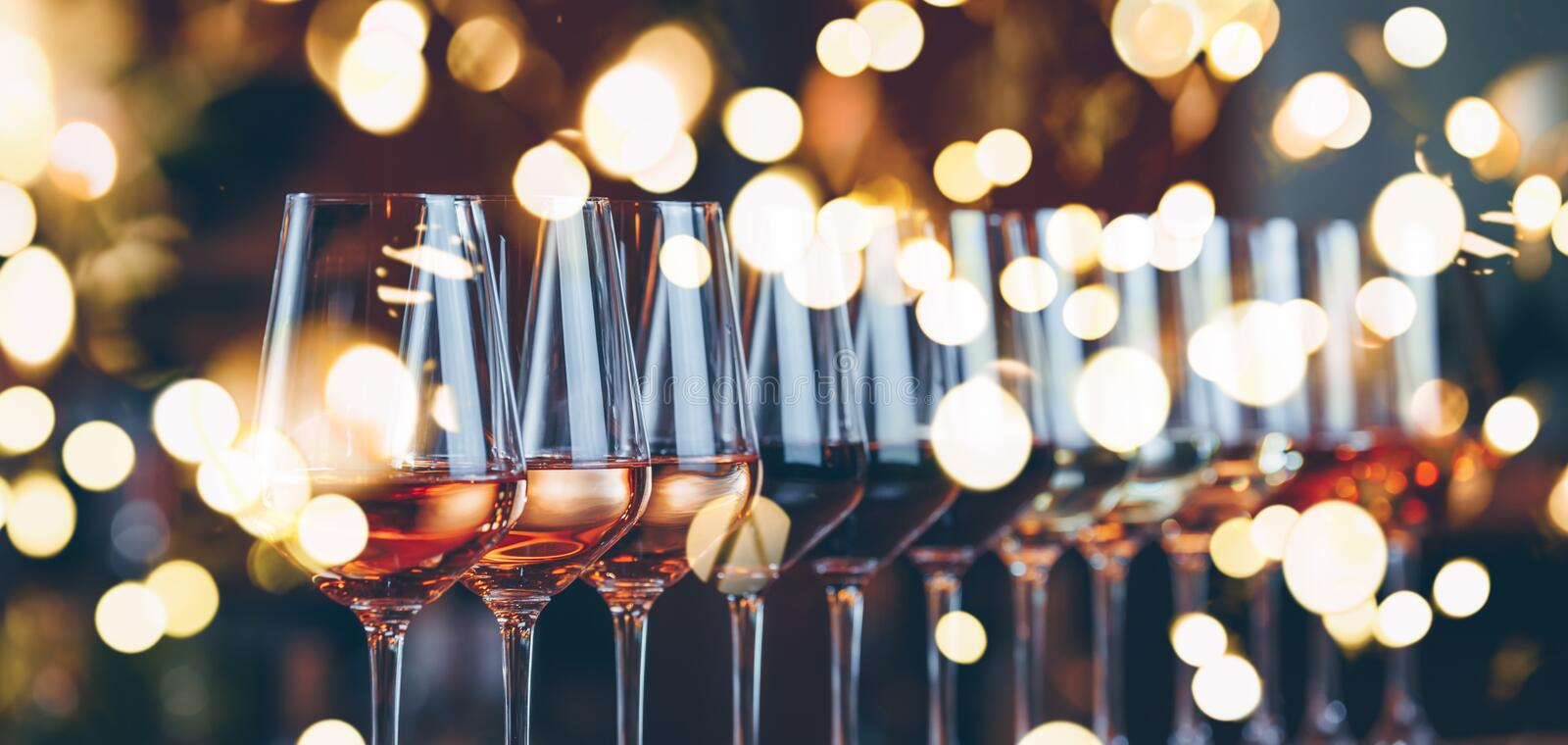 Wine glasses in a row. Buffet table celebration of wine tasting. Nightlife, celebration and entertainment concept. Horizontal, cold toned image, wide screen stock photos