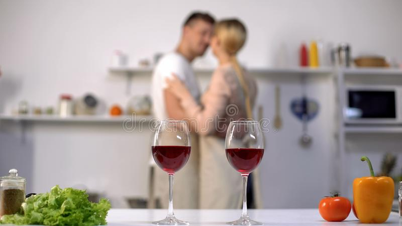 Wine glasses on table, family couple dancing on background, kitchen interior. Stock photo royalty free stock photos