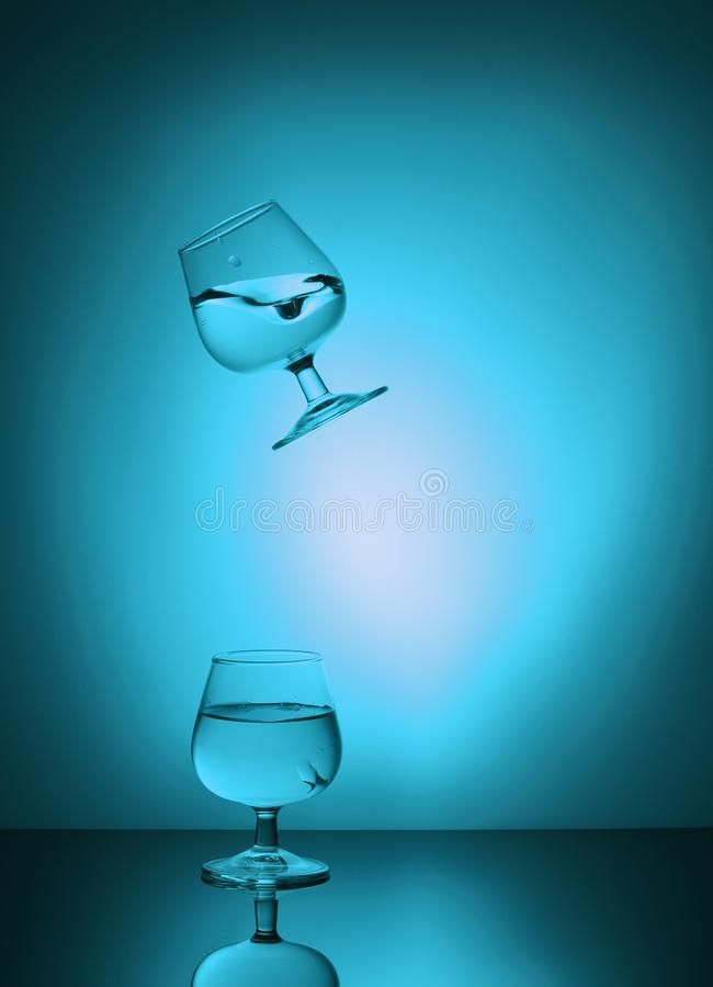 Wine glasses with water falling stock image