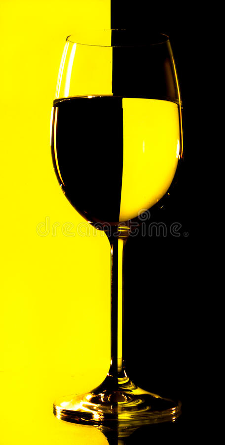 Wine glasses with yellow and black lighted backgro royalty free stock photography