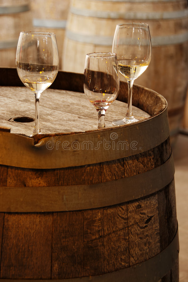 Wine glassess on an old wine barrel. In a winery stock photography
