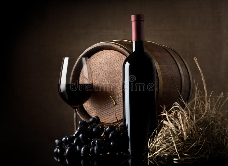 Wine with grape and barrel. On brown background royalty free stock photography