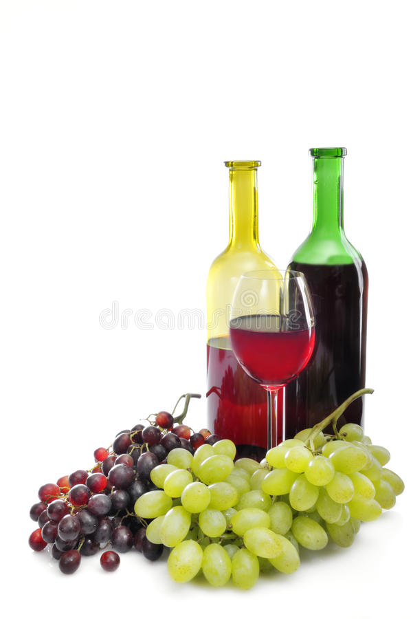 Wine and grapes. Two wine bottles and a glass of wine with red and green grapes at the base. Isolated on a white background royalty free stock images