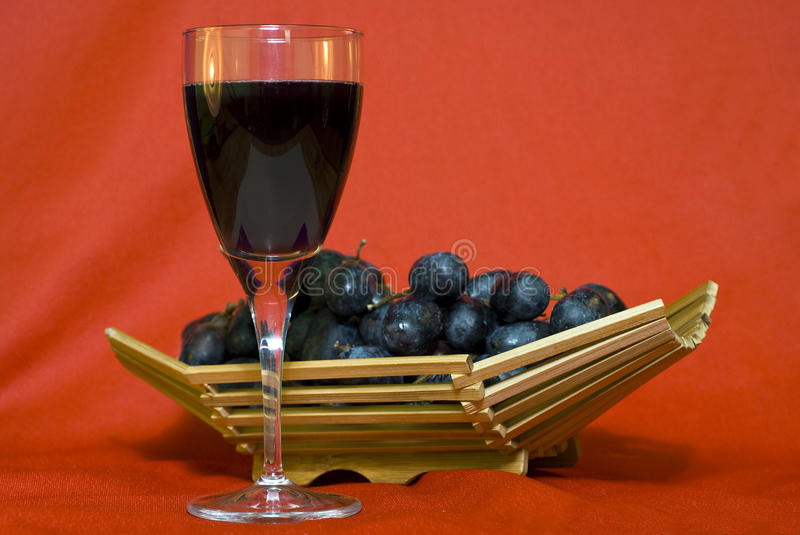 Wine and grapes. On red background royalty free stock image