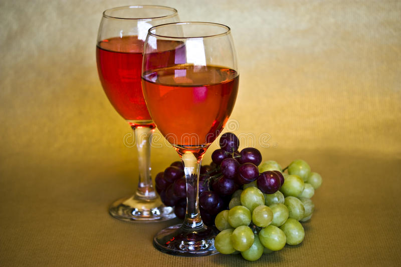 Still life of wine and grapes. A still life of two glasses of red wine and two bunches of grapes royalty free stock images