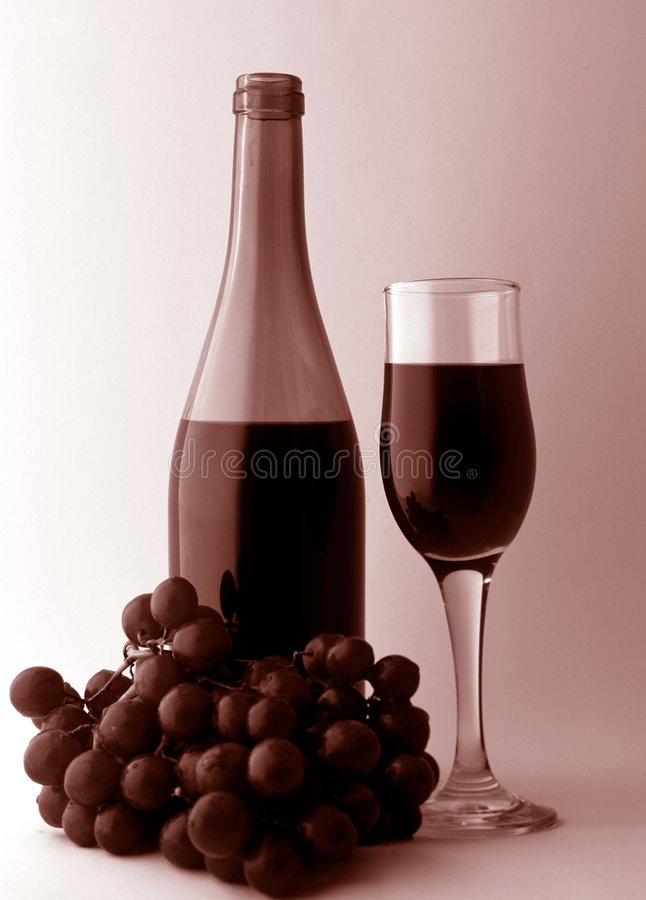 Wine and Grapes. A composition of a bottle of red wine and grapes and glass stock images