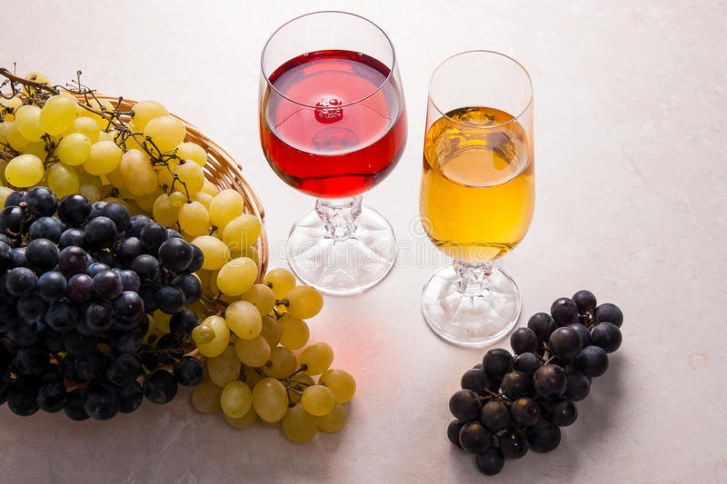 Wine and grapes. White and red wine in glasses on light marble b. Two glasses - one with white wine and one with red wine on light marble background. Bunches of stock photography