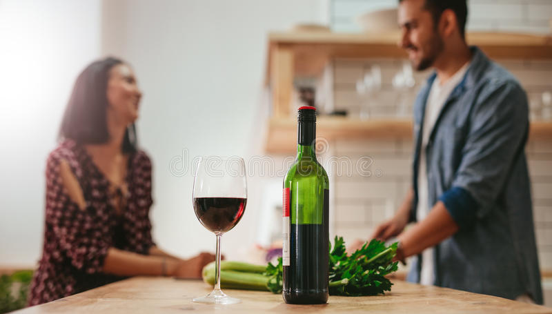 Wine on kitchen counter with couple cooking in background royalty free stock photography