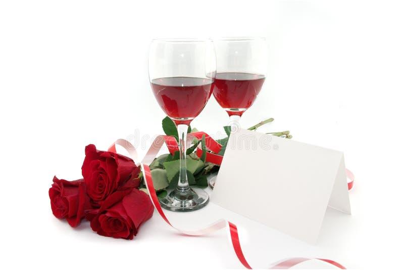 Wine nos vidros, em rosas vermelhas, em fita e no cartão vazio para uma mensagem imagem de stock royalty free