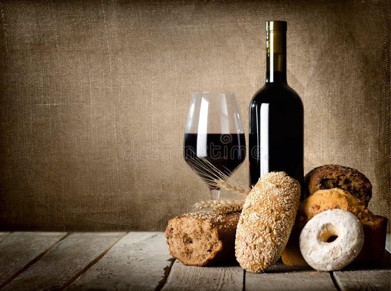 Rött vin och sortiment av bröd royaltyfria foton
