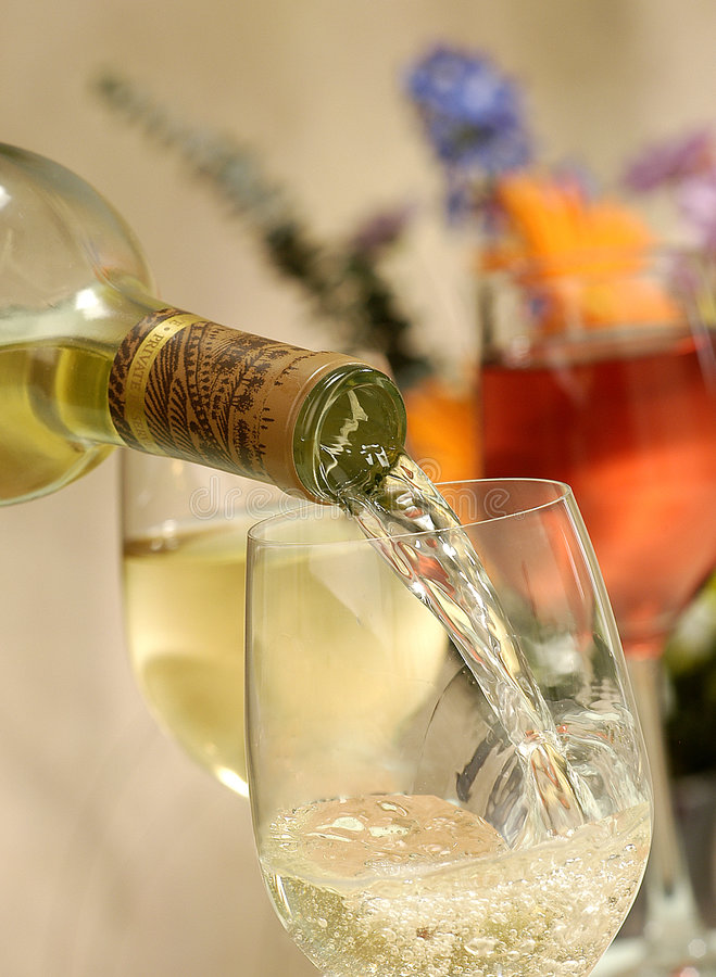 Wine pour. Pouring chardonnay wine, other glasses and flowers in background royalty free stock photography