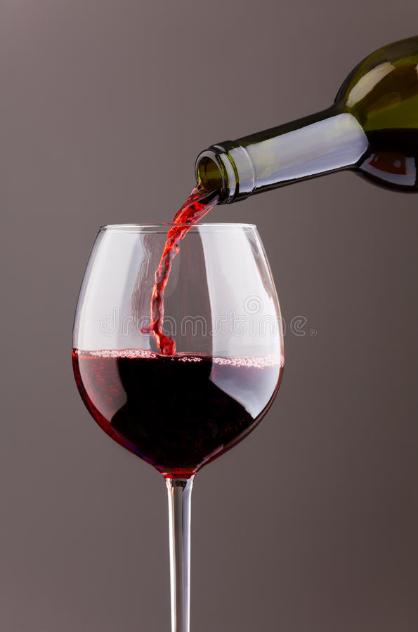Wine pouring in glass on grey background royalty free stock photo