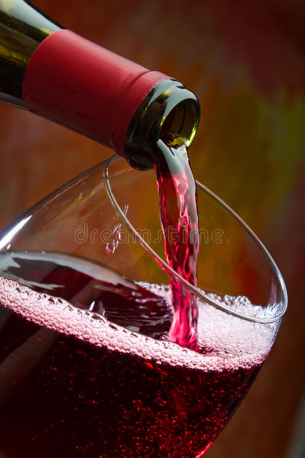 Wine pours into the glass of the bottle stock images