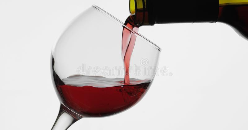 Rose wine. Red wine pour in wine glass over white background royalty free stock images