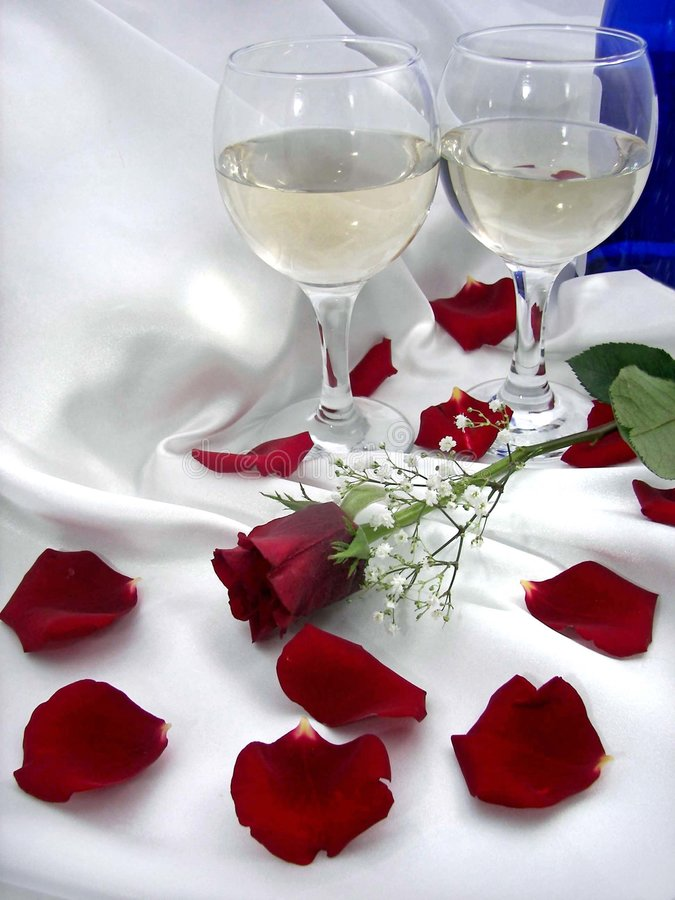 Wine And Roses. Pair of crystal wine glasses with bottle and rose petals on satin royalty free stock photo