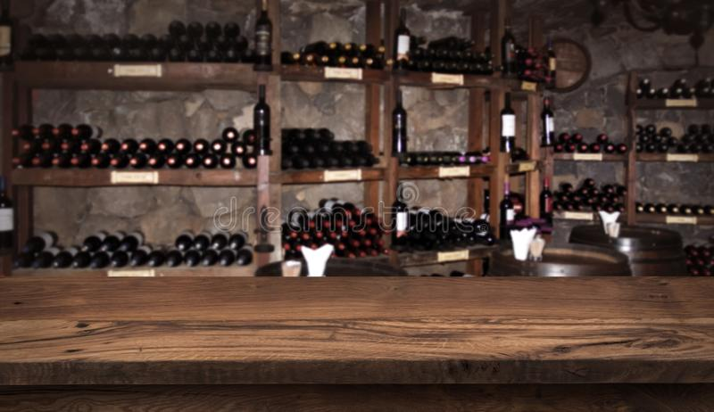 Wine sampling concept. Wooden board before defocused shelfs and barrels stock photo