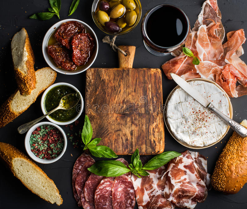 Wine snack set with empty wooden board in center. Glass of red, meat selection, mediterranean olives, sun-dried tomatoes. Baguette slices, camembert cheese and royalty free stock photos