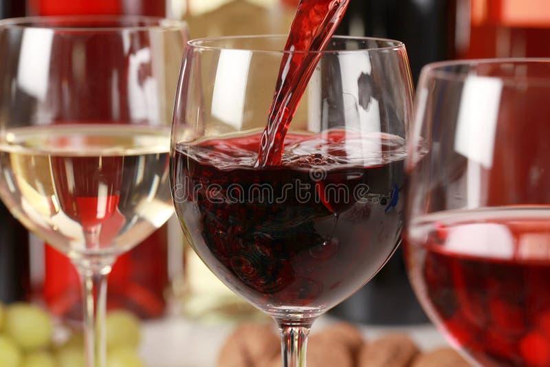 Wine som häller in i ett wineexponeringsglas royaltyfri fotografi
