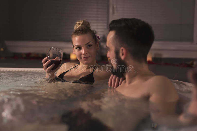 Wine and spa. Couple in love enjoying the romantic atmosphere of a jacuzzi bath, drinking wine and relaxing. Romantic wellness spa getaway royalty free stock image