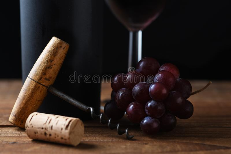 Closeup of an antique cork screw with out of focus red wine bottle, grapes and wineglass in the background, horizontal format stock photography