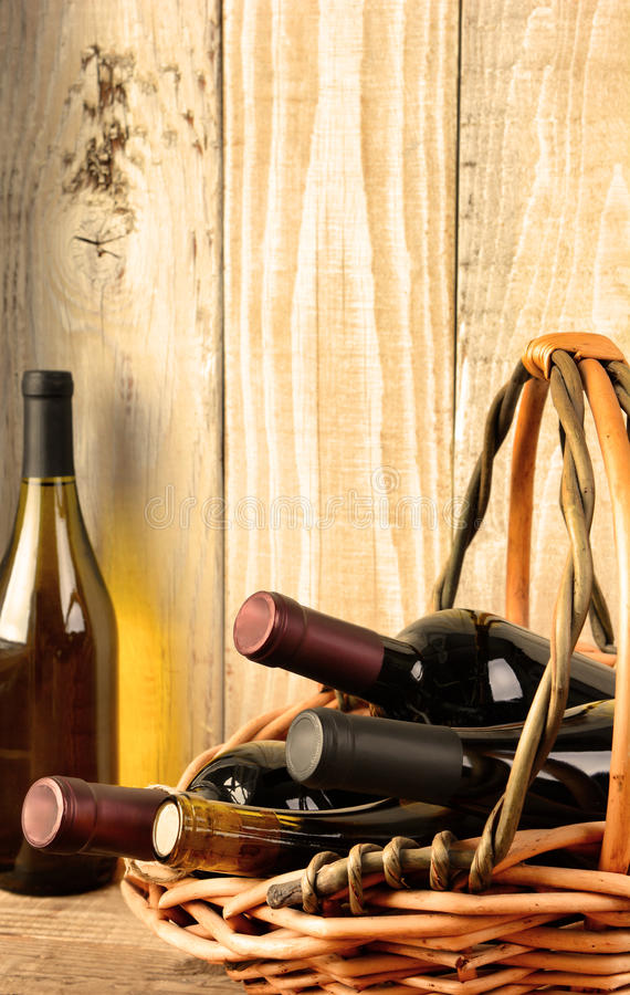 Wine Still Life in Warm Light. Closeup of a wine still life with warm afternoon window light. A basket with assorted bottles and a chardonnay bottle in the stock photo