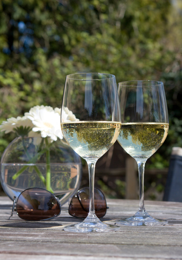 Wine, sunglasses & flowers on wooden patio table. White wine, aviator sunglasses, & flowers on patio table - summertime relaxation stock image
