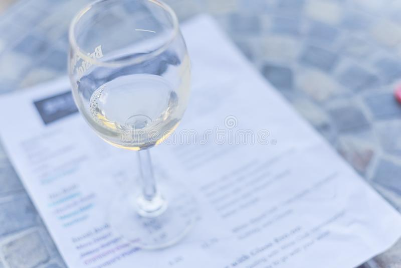 Wine tasting concept with glass of dry white wine and tasting menu. Close-up a glass of sweet white wine and tasting menu with price at local winery in North stock photo