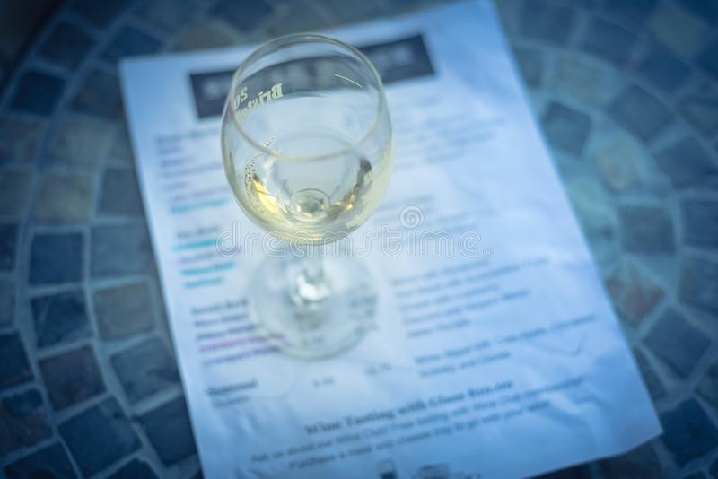 Wine tasting concept with glass of dry white wine and tasting menu. Close-up a glass of sweet white wine and tasting menu with price at local winery in North royalty free stock photography