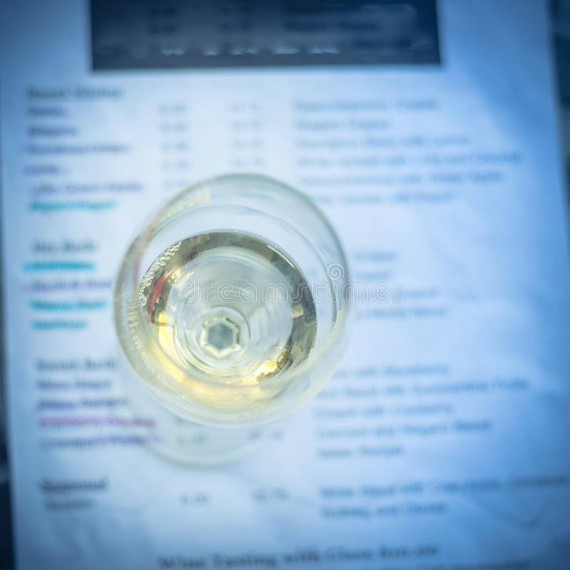 Wine tasting concept with glass of dry white wine and tasting menu. Close-up a glass of sweet white wine and tasting menu with price at local winery in North royalty free stock images