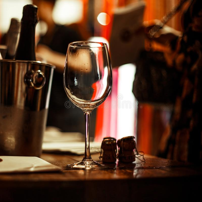 Wine tasting: an empty glass stands on the tasting table next to brochures, champagne corks and silver buckets. Wine tasting: an empty glass stands on the stock photo