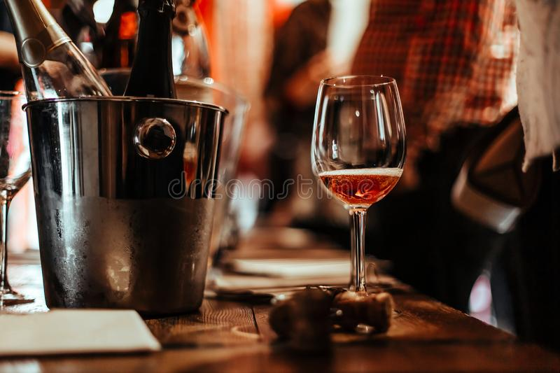Wine tasting: an empty glass stands on the tasting table next to brochures, champagne corks and silver buckets. Wine Tasting: a glass of rose wine stands on the stock image