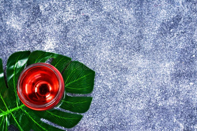 Wine in a wineglass and a tropical leaf. Top view. Wine drink on a gray background. Copy space. royalty free stock photo