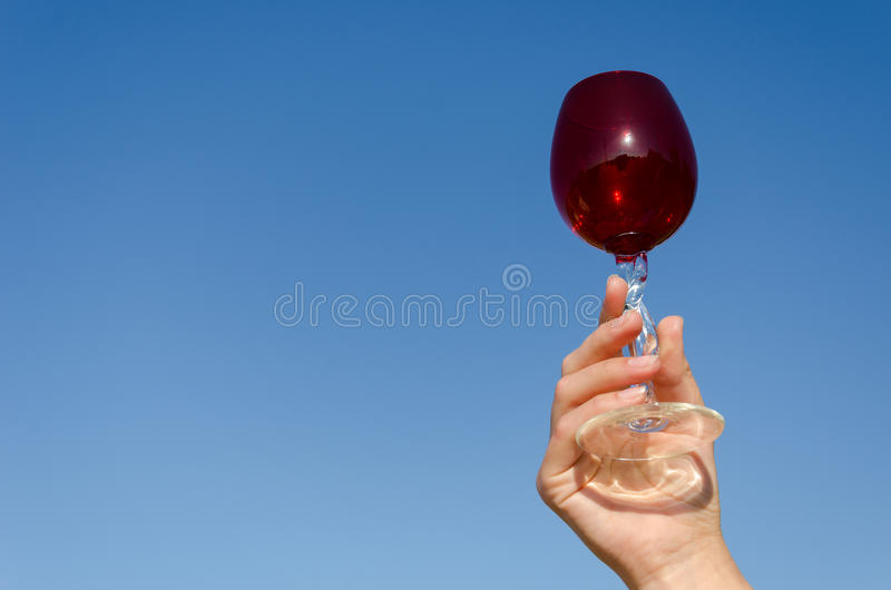Wineglass λαβής χεριών κόκκινος squirm μίσχος στο μπλε ουρανό στοκ φωτογραφία