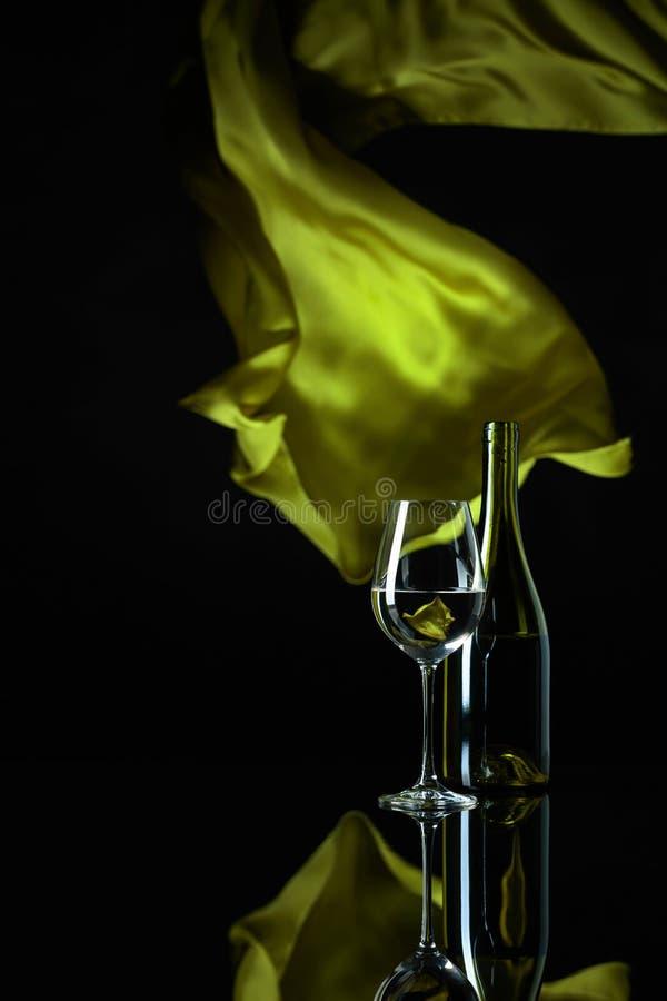 Wineglass και μπουκάλι του άσπρου κρασιού σε ένα μαύρο αντανακλαστικό υπόβαθρο στοκ εικόνες με δικαίωμα ελεύθερης χρήσης