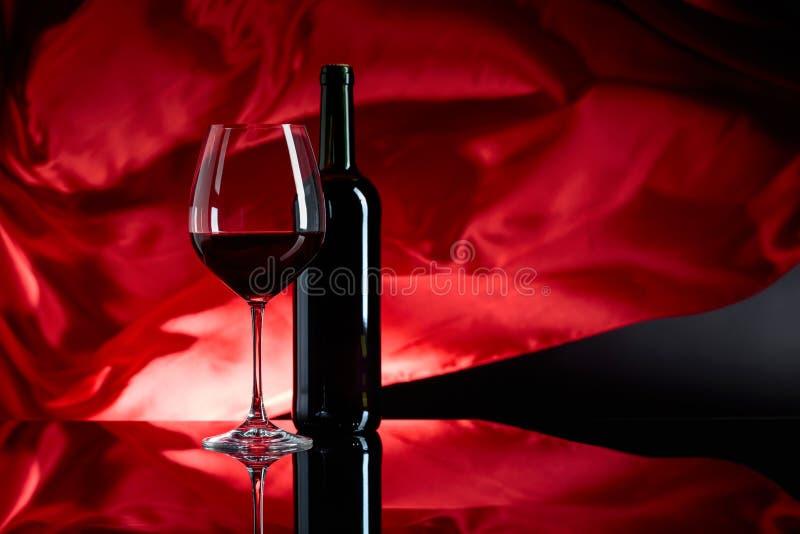 Wineglass και μπουκάλι του κόκκινου κρασιού σε ένα μαύρο αντανακλαστικό υπόβαθρο στοκ φωτογραφίες με δικαίωμα ελεύθερης χρήσης