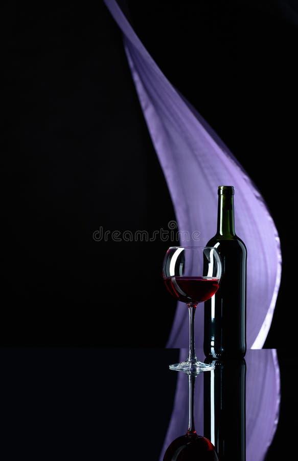 Wineglass και μπουκάλι του κόκκινου κρασιού σε ένα μαύρο αντανακλαστικό υπόβαθρο στοκ φωτογραφία