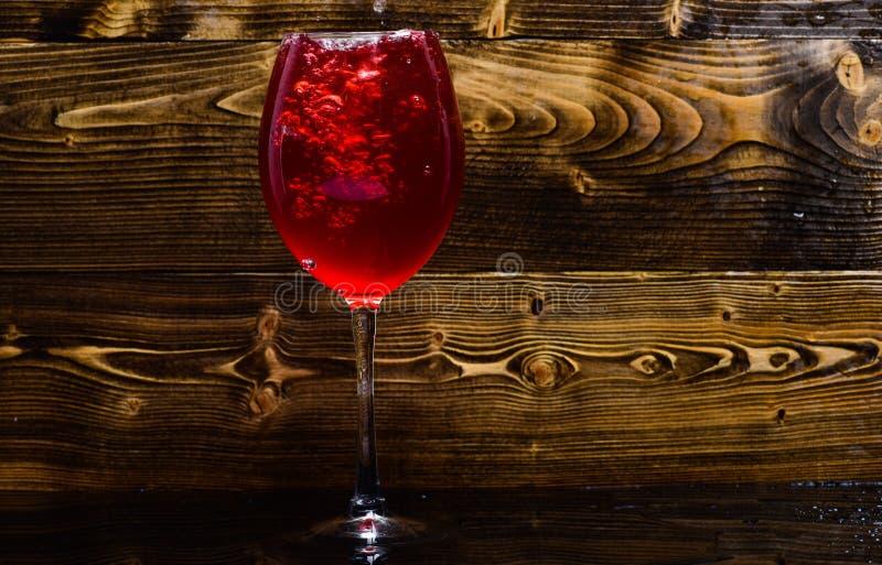 Wineglass που γεμίζει με το νερό με τους παφλασμούς στο σκοτεινό ξύλινο υπόβαθρο Αναζωογονώντας έννοια ποτών Γυαλί με την έκχυση  στοκ εικόνες
