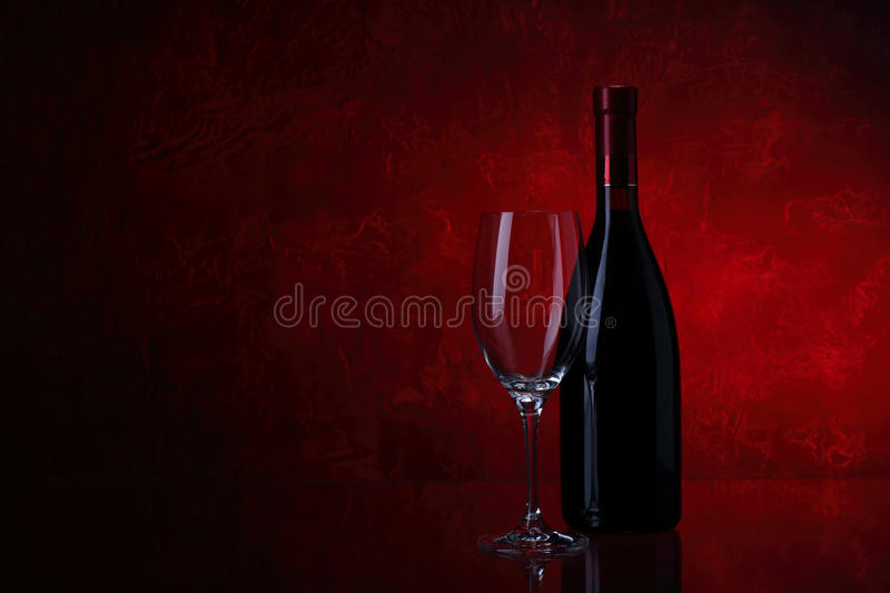 Wineglass and bottle of red wine stock photography