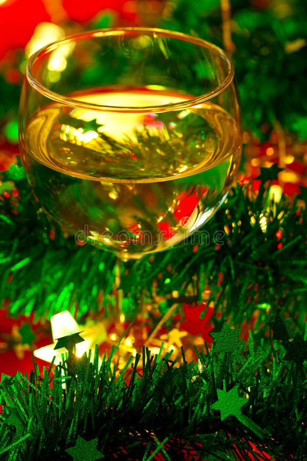 Wineglass with Christmas decoration. Glass of white wine with Christmas decoration, very shallow DOF stock photography