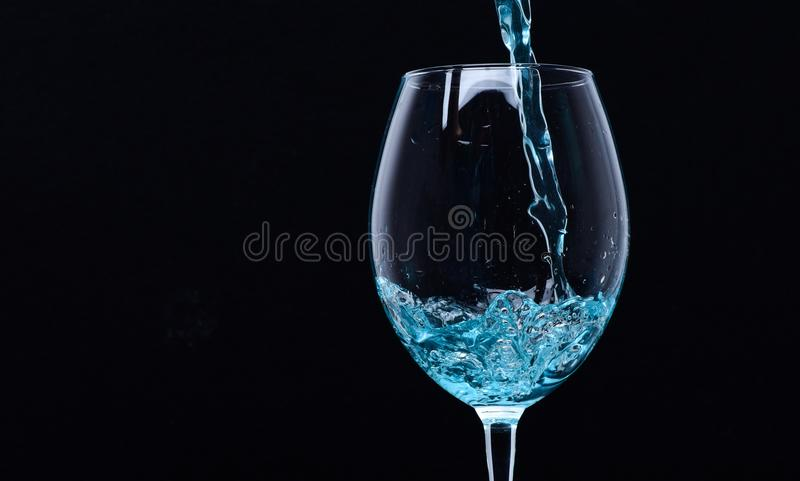 Wineglass filling with water with splashes on black background. Refreshing drink concept. Glass with blue water pouring stock image
