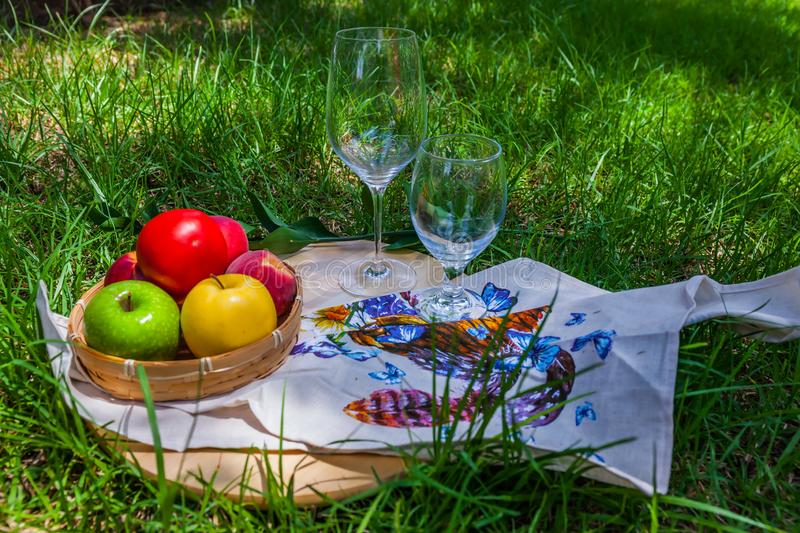 The wineglass and napkin. Breakfast on the grass. Concept of artistic photography. Sunny summer day. Fruits - apples and peach - in a wicker basket, wineglasses stock photography