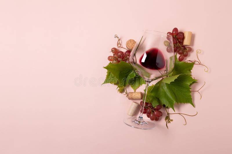 Wineglass with red wine, grape, leaves and cork lying on pink background. Wine degustation concept. Flat lay. Top view. Copy space.  stock photography