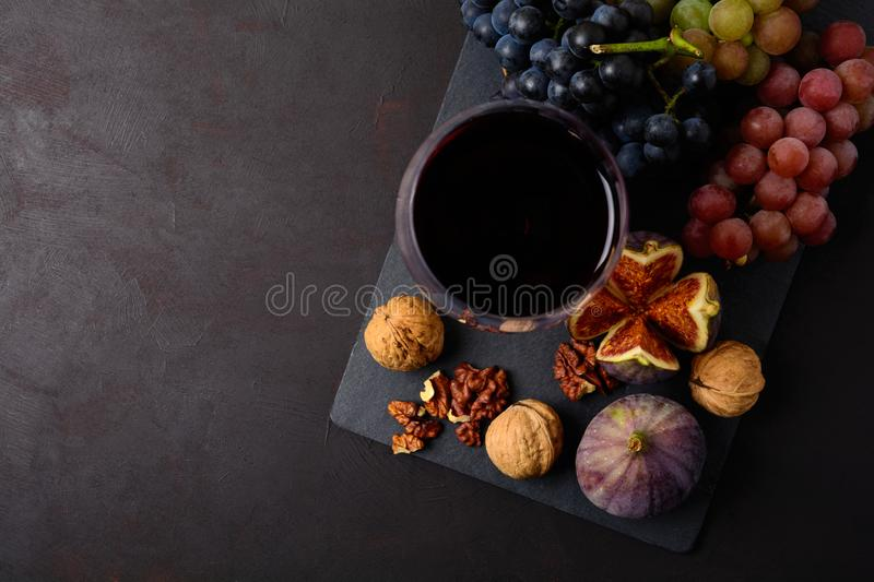 Wineglass with red wine, grapes, figs and walnuts lying on dark wooden background. Top view. royalty free stock images
