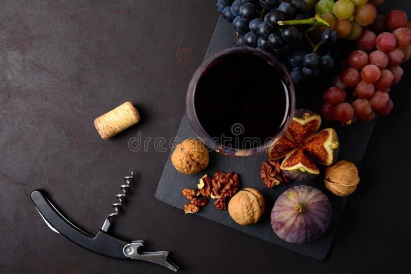 Wineglass z czerwonego wina, winogron, fig, orzechów włoskich, korka i corkscrew lying on the beach na ciemnym drewnianym tle, Od zdjęcia stock