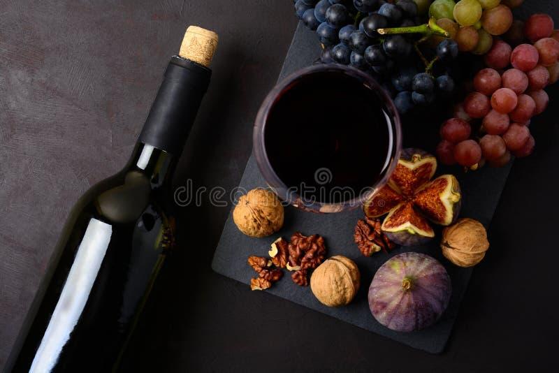 Wineglass z czerwonym winem, butelką, winogronami, figami i orzechami włoskimi kłama na ciemnym drewnianym tle, Odgórny widok fotografia stock