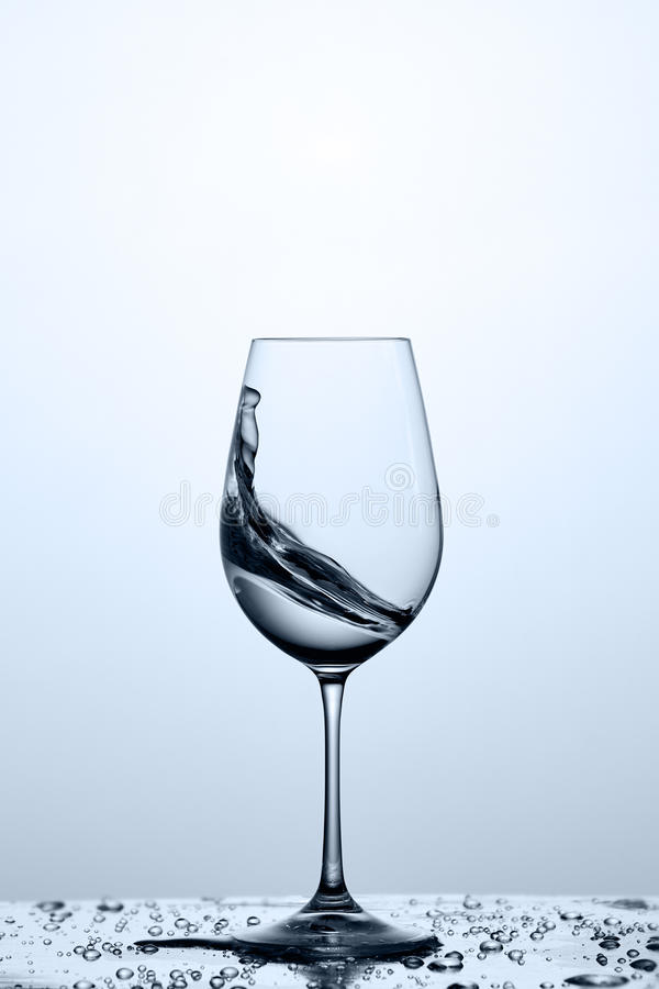 Wineglass z przejrzystym wodnym pluśnięciem na szkle z kropelkami przeciw lekkiemu tłu obrazy royalty free