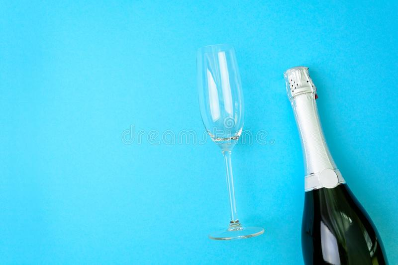 Wineglasses and bottle of champagne lying on blue paper background. New Year celebration concept. Top view. Flat lay stock photos